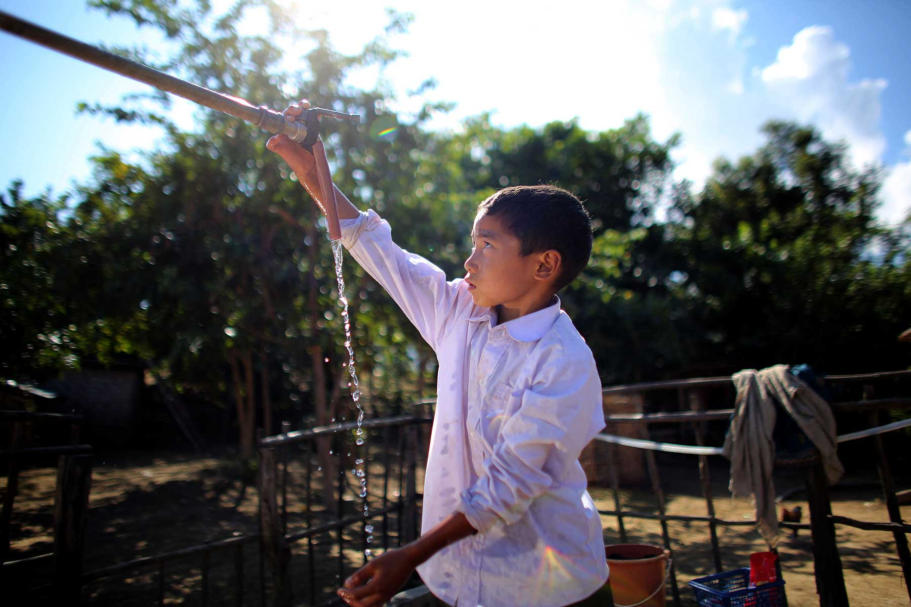 A Lao village boy washes his hands under the village tap